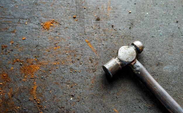 Vieux marteau de fer sur bois avec flou artistique et lumière en arrière-plan. vue de dessus