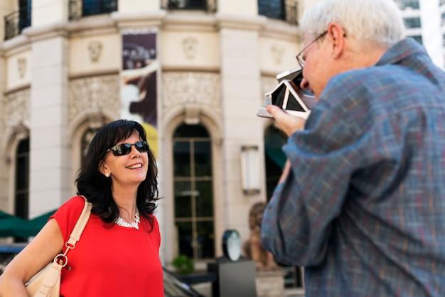 Vieux mec prenant une photo de son fond de ville femme