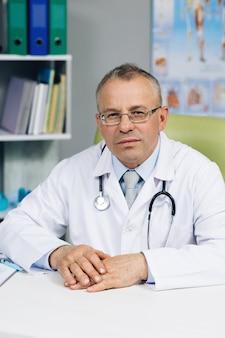 Vieux médecin-chef mâle mature en uniforme médical blanc dans des verres assis sur le lieu de travail.