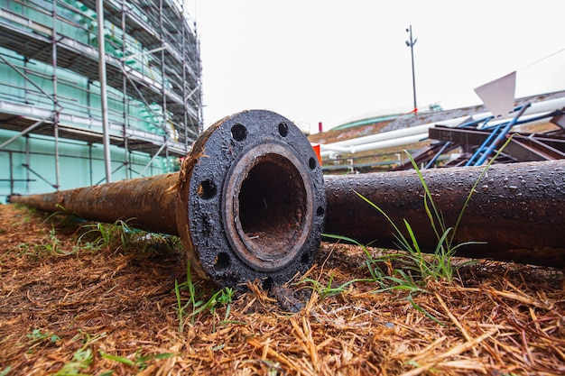 Vieux métal de corrosion de canalisation de pétrole se trouvant dans le tuyau latéral l'asphalte
