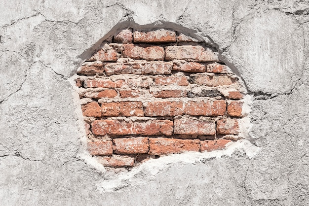 Vieux modèle de briques sur le mur de béton fissuré grunge. abstrait