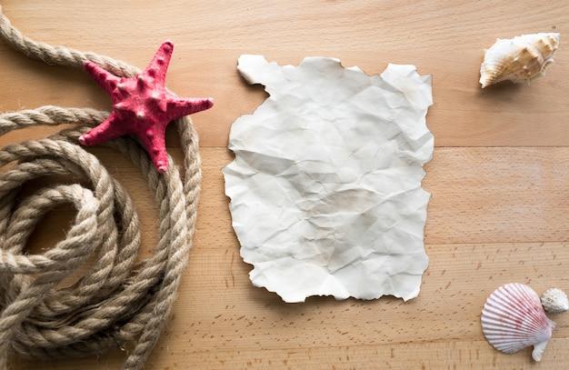 Vieux morceau de papier vierge allongé sur des planches de bois avec des cordes et des coquillages