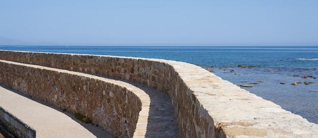 Un vieux mur ancien avec un ciel bleu clair et une mer floue en arrière-plan à la canée.