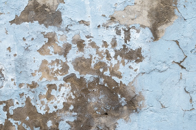 Vieux mur de béton avec peinture écaillée. gros plan sur un mur de ciment en ruine bleu. texture abstraite de stuc grunge. surface de plâtre fissurée.