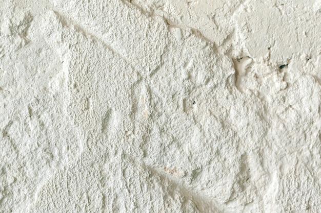 Vieux mur blanc rugueux avec des fissures pour un fond