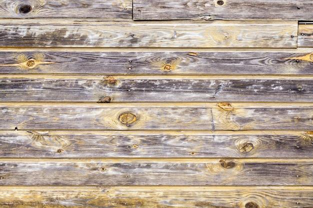 Vieux mur en bois à peine peint, maison rurale