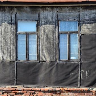 Vieux mur de brique patiné avec des fenêtres