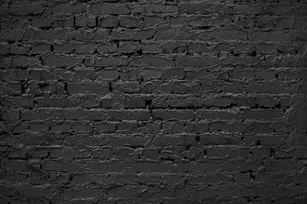 Vieux mur de briques. abstrait noir. texture de briques noires. surface du mur rugueuse sombre.