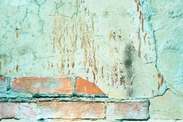 Vieux mur de briques. béton fissuré. texture turquoise, bleu, marron. fond vintage