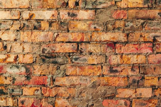 Vieux mur de briques brunes patinées pour le fond
