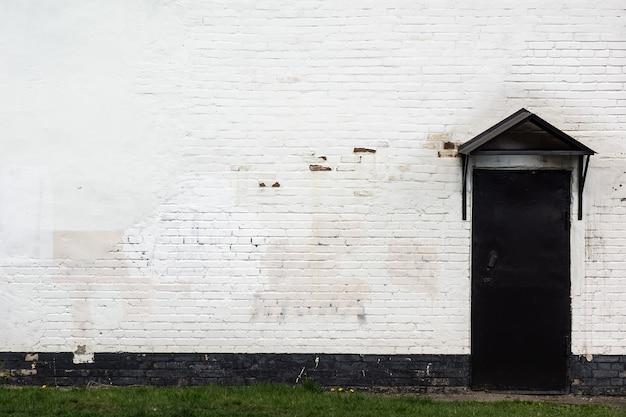 Vieux mur de briques brutes et porte en noir avec une visière