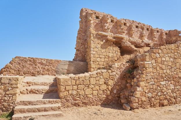 Un vieux mur de briques avec des escaliers et un ciel bleu clair en arrière-plan.