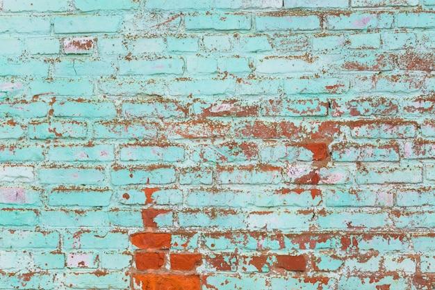 Vieux mur de briques peintes en vert.