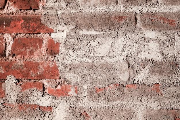 Vieux mur de briques rouges avec du plâtre blanc. surface rugueuse et endommagée, style loft. fond vintage.
