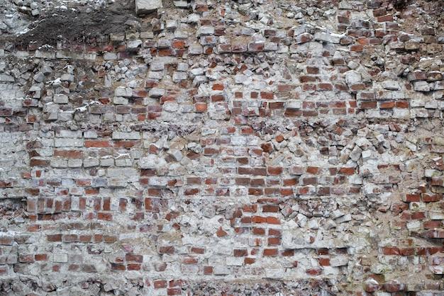 Vieux mur de briques rouges en ruine à l'extérieur. tir lointain. fond de texture