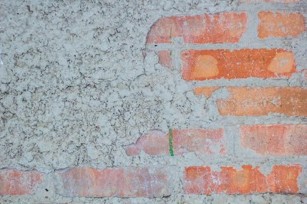 Vieux mur de briques rouges vintage avec fond de texture de plâtre blanc saupoudré