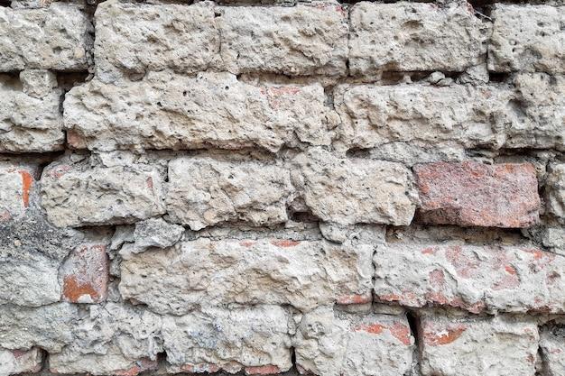 Vieux mur de briques sous une couche de plâtre