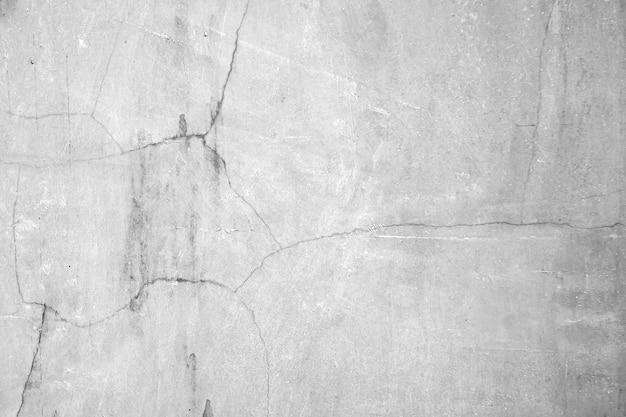 Vieux mur de ciment ou de béton ou de plâtre brut avec des taches et des fissures pour le fond et la texture.