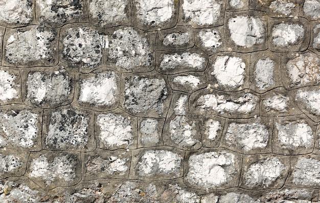 Vieux mur de construction fait de pierres brutes