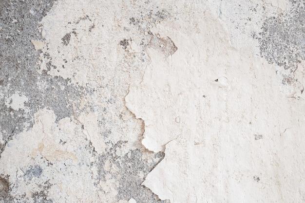 Vieux mur endommagé par du plâtre soufflé et des obstructions de peinture, des dégâts de peinture écaillés, des dégâts d'eau sur le mur du bâtiment abstrait grunge