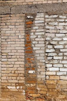 Un vieux mur fait de briques de différents types et tailles, un gros plan d'une partie du mur fait de briques