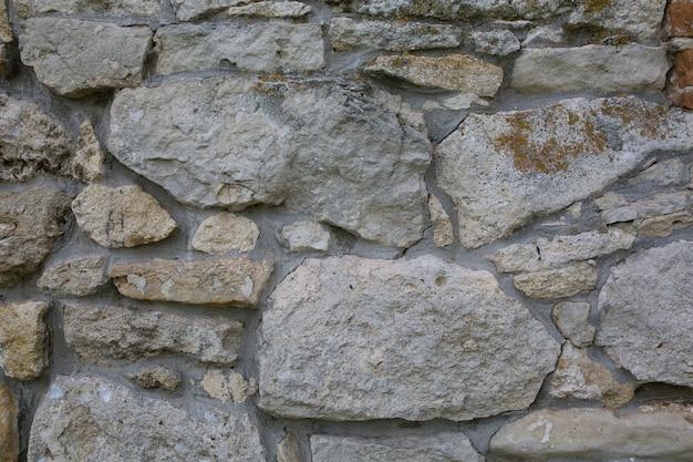 Vieux mur de grosses pierres et de briques cassées. vintage surface des blocs bruts