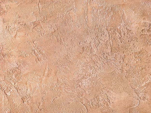 Vieux mur orange recouvert de plâtre inégal, texture de la surface de brique de sable minable vintage,