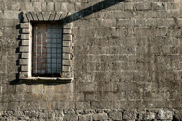 Vieux mur de pierre avec fenêtre et grille