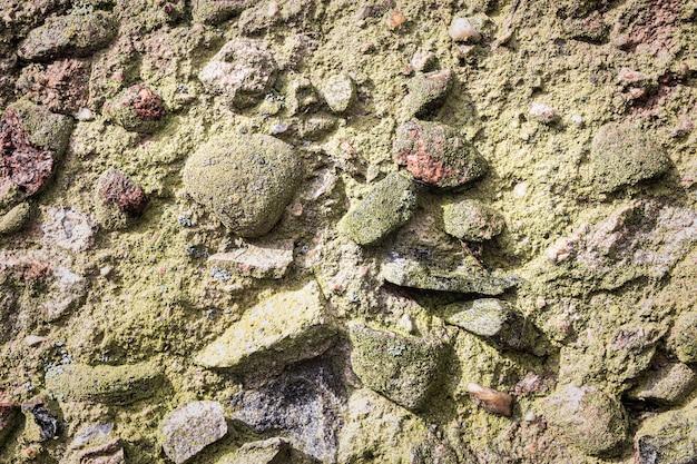 Vieux mur de pierre de granit texturé de grosses pierres moussues grises en arrière-plan.