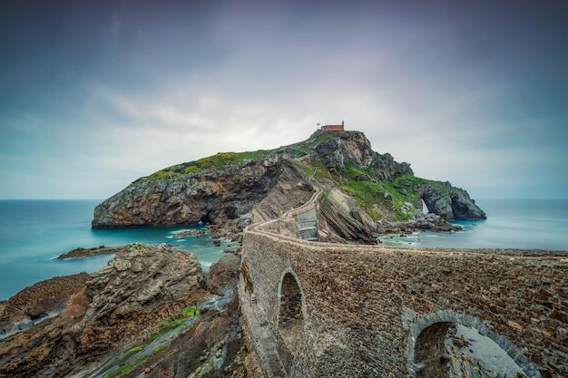 Vieux mur de pierre passant sur l'océan jusqu'à une île