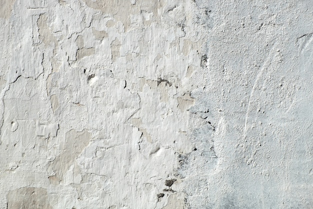 Vieux mur de plâtre fissuré, fond texturé blanc