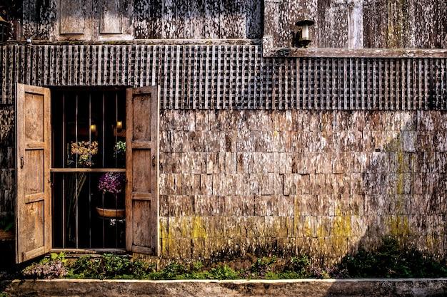 Les vieux murs de maison en bois ouvrent de grandes fenêtres.