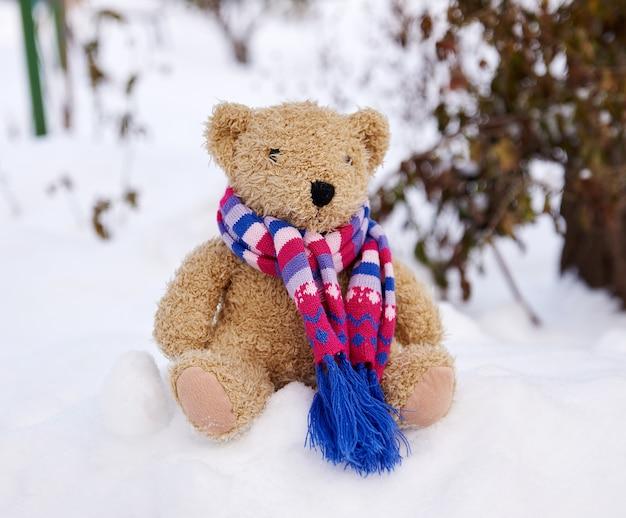 Vieux ours en peluche dans une écharpe est assis sur la neige blanche