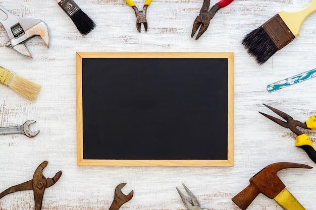 Vieux outils à main rouillés avec tableau noir