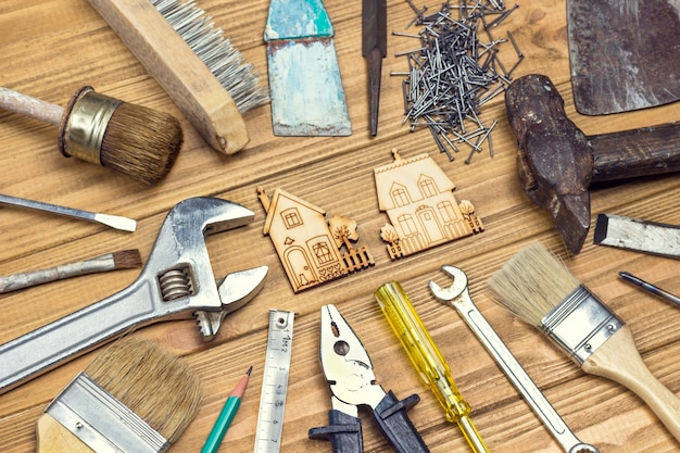 Vieux outils de maison poussiéreux pour les travaux de réparation. fond en bois clair. mise à plat