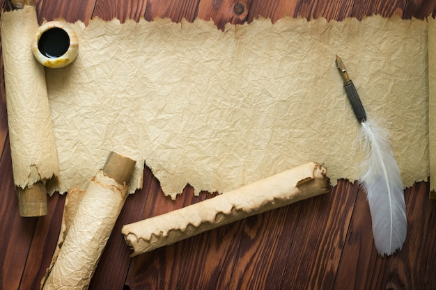 Vieux papier, parchemin et plume sur papier en bois avec espace copie