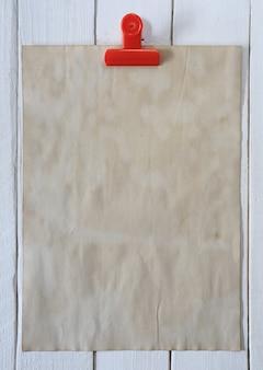 Vieux papier vintage brun et un trombone rouge sur un plancher en bois blanc.