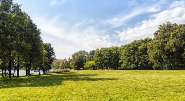 Vieux parc avec des pelouses vertes et de grands arbres.