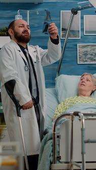 Vieux patient atteint d'une maladie recevant la visite d'un médecin