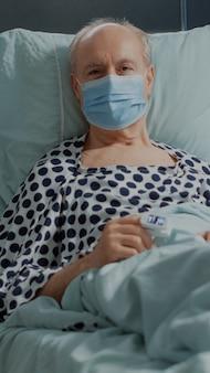 Vieux patient avec masque facial et oxymètre