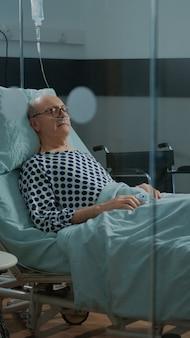 Vieux patient souffrant de problèmes respiratoires assis dans la salle d'hôpital