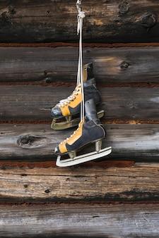 Vieux patins accroché au mur en bois