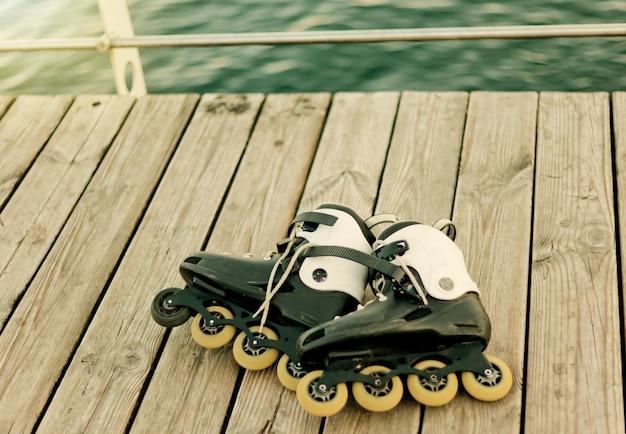 Vieux patins à roulettes sur une terrasse de plage contre la mer