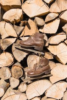 Vieux patins suspendus sur une pile de bois de chauffage
