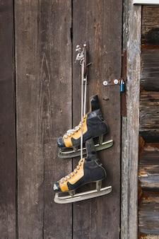 Vieux patins suspendus à une porte en bois