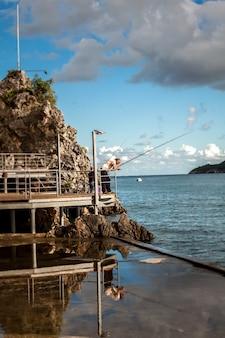 Vieux pêcheur debout avec une tige sur une jetée en bois au rivage rocheux