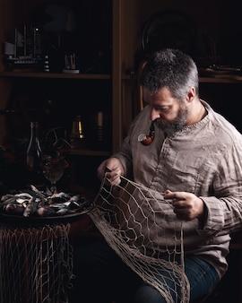 Vieux pêcheur réparant son filet