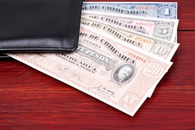 Vieux pesos mexicains dans le portefeuille noir