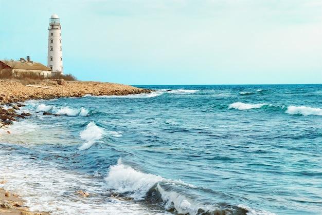 Vieux phare sur la côte de la mer. tempête, vagues et ciel bleu.