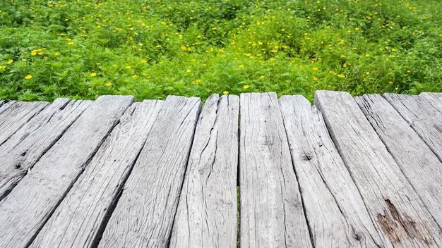 Vieux plancher en bois avec champs de fleurs cosmos jaune